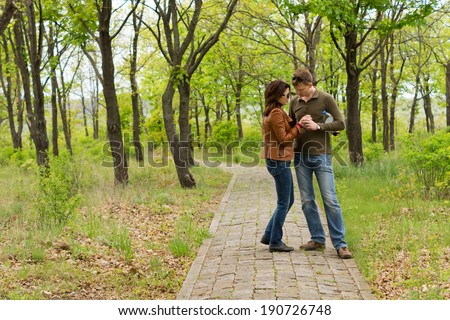 Loving couple standing close together holding hands on a path through woodland as they enjoy a tender intimate moment - stock photo