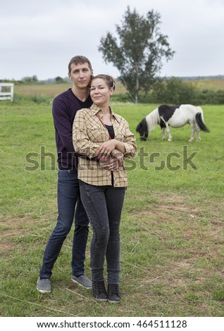 Loving couple standing in farm with pony horse on background
