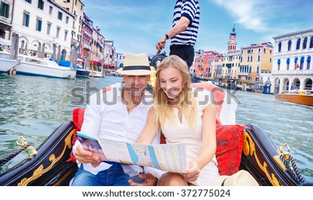 Loving couple traveling to Venice, searching on the map place with famous sightseeing, riding on a gondola on the Grand Canal, vacation in Italy, enjoying holidays in Europe - stock photo