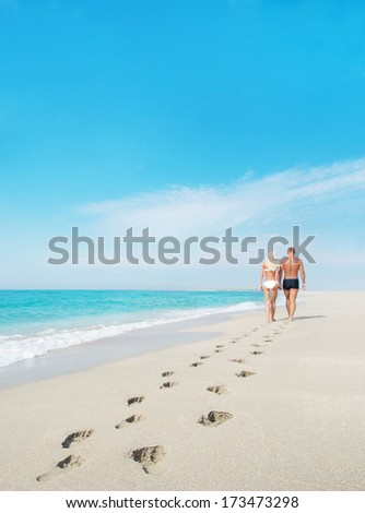 loving couple walking away with footprints at sea sandy beach - stock photo