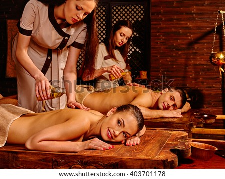 Loving couple  with a soothing ayurvedic spa treatment. Oil massage in  Spa salon. Spa salon decoreted bamboo. - stock photo