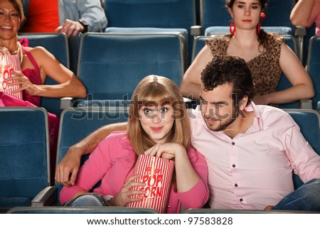 Loving couple with bag of popcorn in theater - stock photo