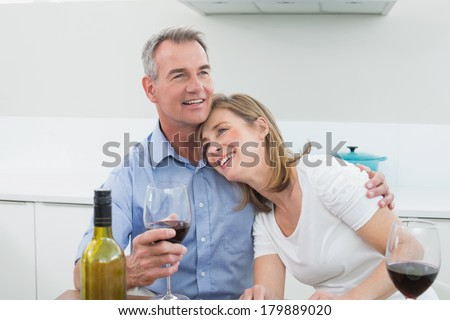 Loving couple with wine glasses in the kitchen at home - stock photo