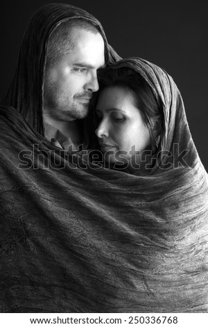Loving couple wrapped in a shawl, monochrome - stock photo