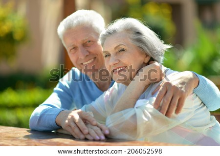 Loving cute elder couple on nature background