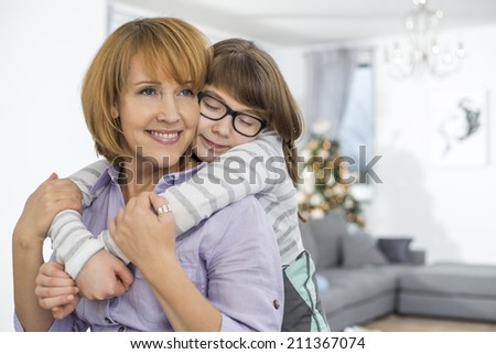 Loving daughter embracing mother at home - stock photo