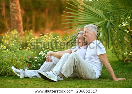 Loving elder couple sitting near flowers and palms
