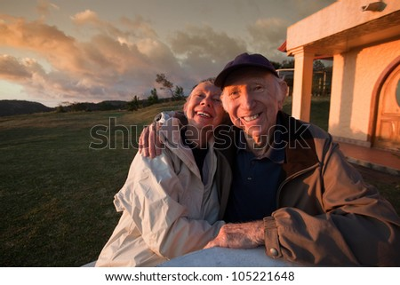 Loving elderly couple smiling at table in mountains - stock photo