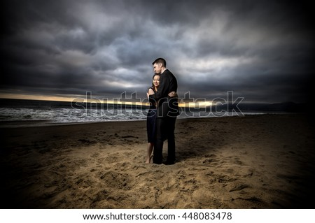 Loving engaged couple on honeymoon in a dramatic HDR beach island landscape.  The sky looks moody.