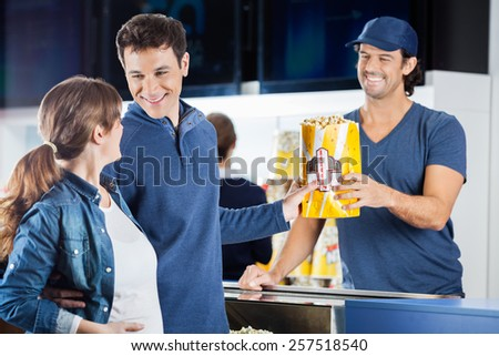 Loving expectant couple buying popcorn from male seller at concession stand in cinema - stock photo
