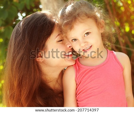 Loving family. Beautiful mother and happy smiling kid girl outdoors. Closeup portrait