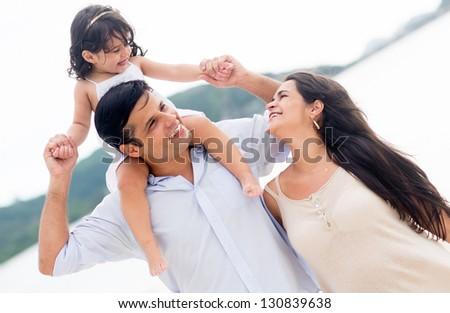 Loving family enjoying their time at the beach - stock photo