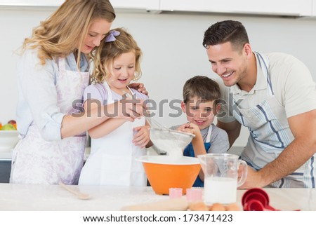 Loving family of four preparing cookies at kitchen counter