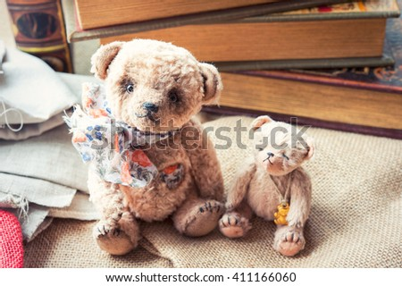 Loving family of two small vintage handmade textile sweet teddy bear art toys together with old books background. Indoors closeup horizontal close up image with retro filter. - stock photo