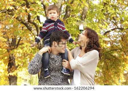 Loving family standing in the park. Shallow focus. - stock photo