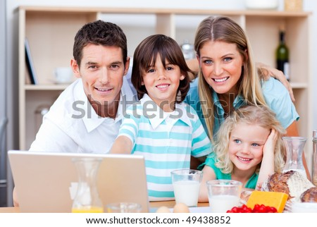 Loving family using laptop during the breakfast in the kitchen - stock photo