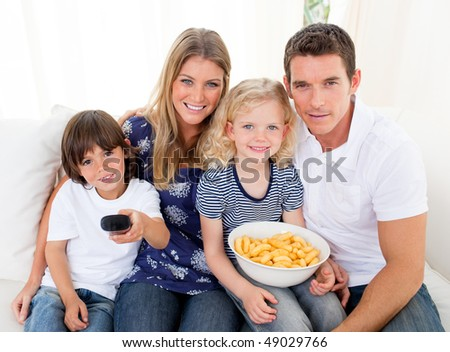 Loving family watching television sitting on sofa at home - stock photo