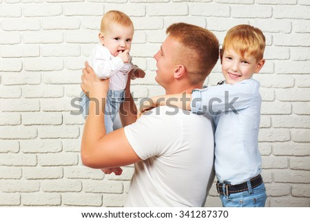Loving father and two sons on the background of brick wall - stock photo