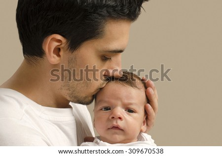 Loving father kissing his new born baby. Father kissing his baby boy forehead and holding him. Parent love. - stock photo