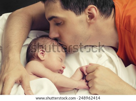 Loving father kissing his new born baby.Father kissing his baby boy forehead while his sleeping and holding hands. Parent love. - stock photo