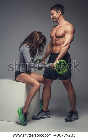 Loving fitness couple posing in a studio.
