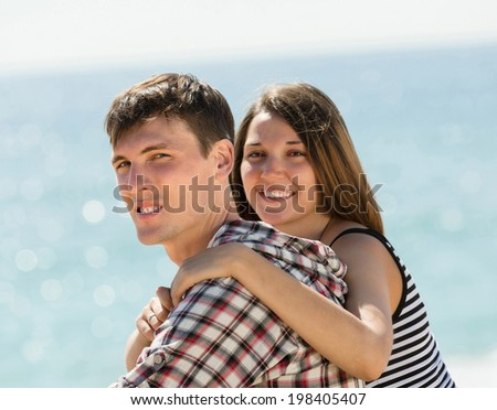 Loving girl and her boyfriend embrace at sandy beach