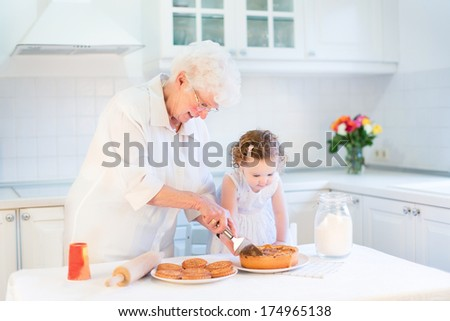 Loving grandmother baking an apple pie with her adorable toddler granddaughter in a beautiful white kitchen - stock photo