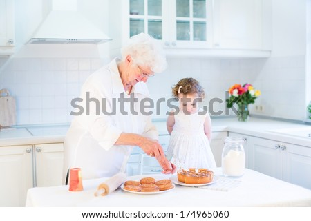 Loving grandmother baking an apple pie with her adorable toddler granddaughter standing in a beautiful white kitchen - stock photo