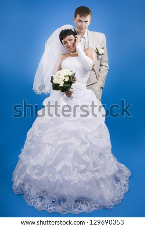Loving groom and beautiful bride are happy together. Blue background.