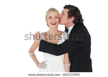 Loving groom kissing attractive bride over white background