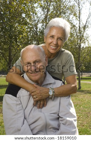 Loving, handsome senior couple relaxing in the park - stock photo