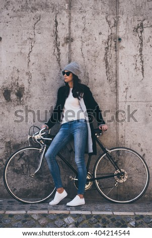 Loving her new style. Beautiful young woman in sunglasses holding hands on her bicycle and looking away while standing against concrete wall outdoors - stock photo