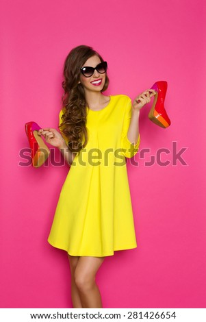 Loving High Heels. Smiling young woman in yellow mini dress and sunglasses holding two red high heels. Three quarter length studio on pink background. - stock photo