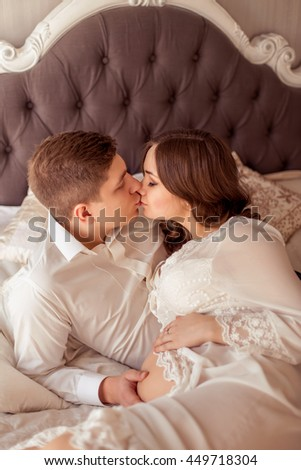 Loving husband gently kissing and hugging his pregnant wife and touches her tummy. Happy family in anticipation of the birth of the baby.