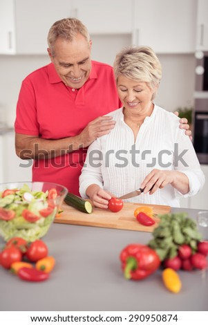 Loving Husband Watching his Happy Wife Slicing Fresh Salad Ingredients for Dinner at the Kitchen - stock photo