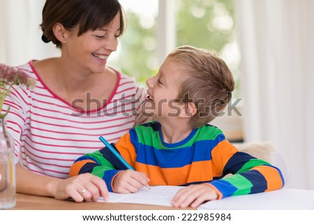 Loving little boy smiling at his mother as she sits at the table with him at home helping him with his school work - stock photo