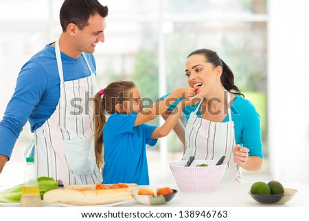loving little daughter feeding mother a piece of tomato while cooking with father