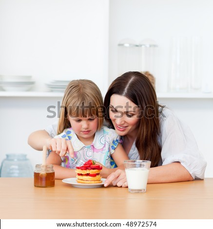 Loving little girl and her mother having breakfast in the kitchen - stock photo