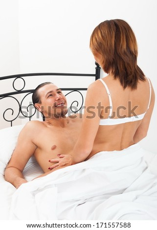 Loving man and woman in bed in bedroom - stock photo