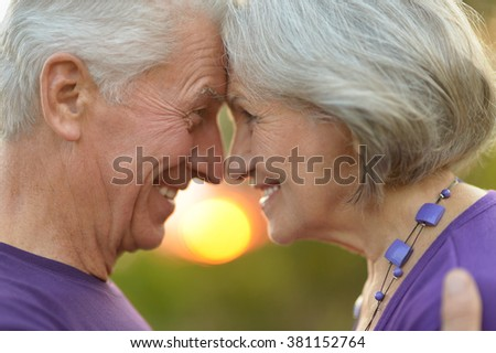 Loving mature couple  in summer park on the Sunset - stock photo