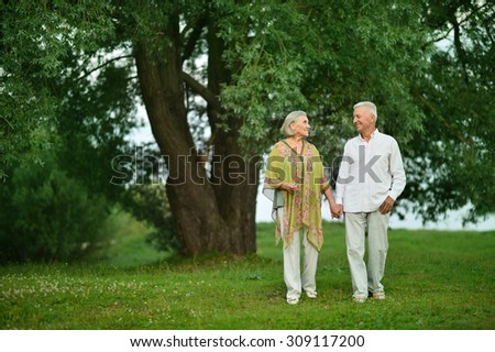 Loving mature couple on a walk in the park in summer - stock photo