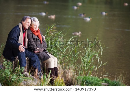 Loving mature couple sitting and looking on the river side - stock photo
