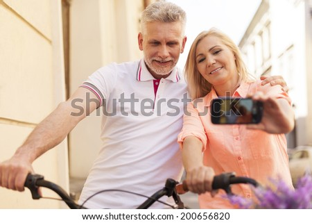 Loving mature couple taking selfie with bike