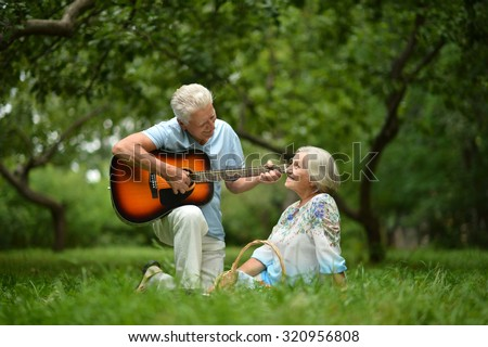 Loving mature couple with guitar   in summer park - stock photo