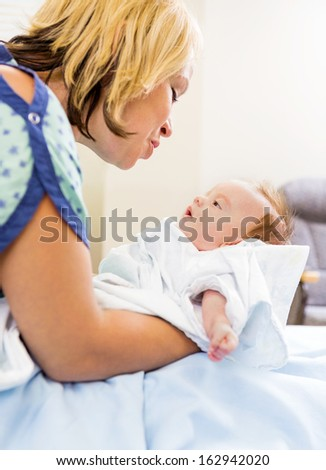 Loving mid adult woman looking at cute newborn babygirl in hospital room