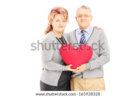 Loving middle aged couple holding a red heart and looking at camera isolated on white background - stock photo