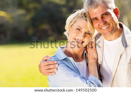 loving middle aged couple hugging outdoors - stock photo