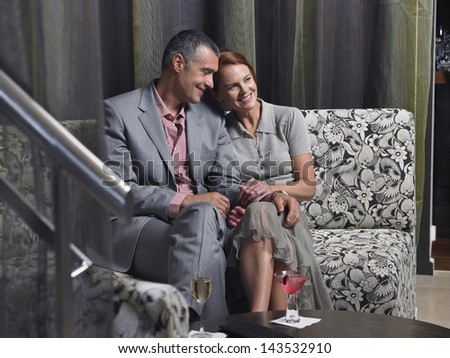 Loving middle aged couple on couch with drinks on coffee table in hotel lobby - stock photo