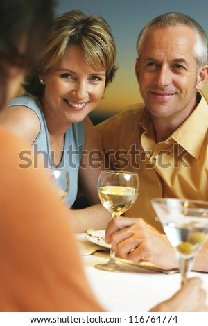 Loving middle-aged couple sitting at the dinner table socialising with friends - stock photo
