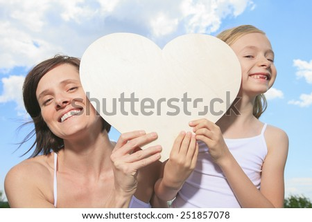 loving mother and daughterr, holding a heart shaped over the cloud - stock photo